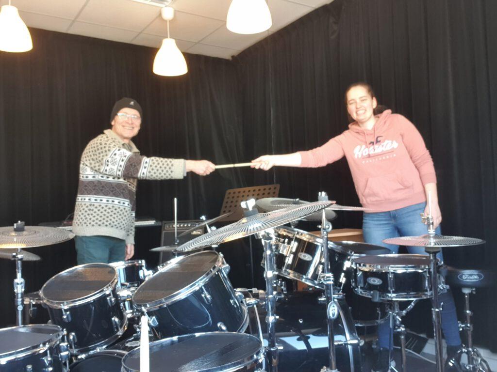 Voormalig eigenaar J.G.M. Nühn geeft letterlijk en figuurlijk het (drum)stokje door aan de nieuwe eigenaar Marit van der Burgh (Muziekschool De Brug)